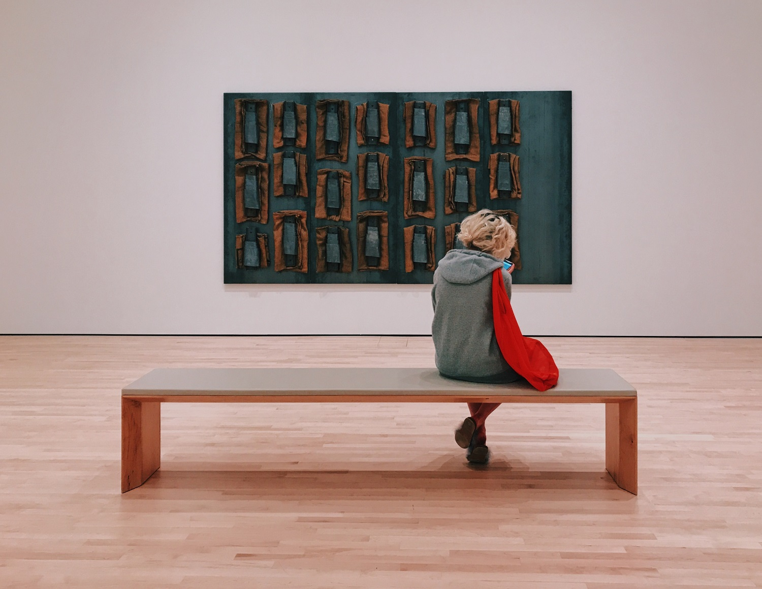 A woman sits on a long backless bench in front of a contemporary art piece.