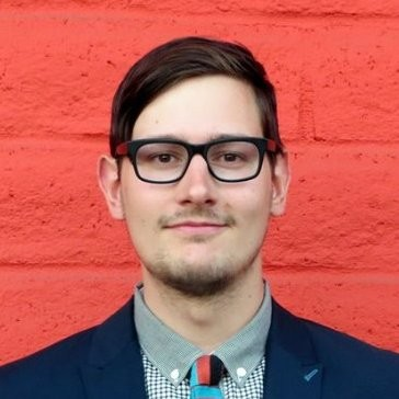A white male stands in front of a red cinderblock wall looking straight at the camera wearing dark rimmed glasses a suit and tie.