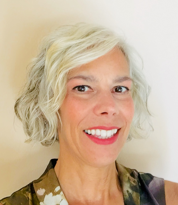 Headshot of Lori standing against a white wall. A white woman with short gray hair wearing bright pink lipstick.
