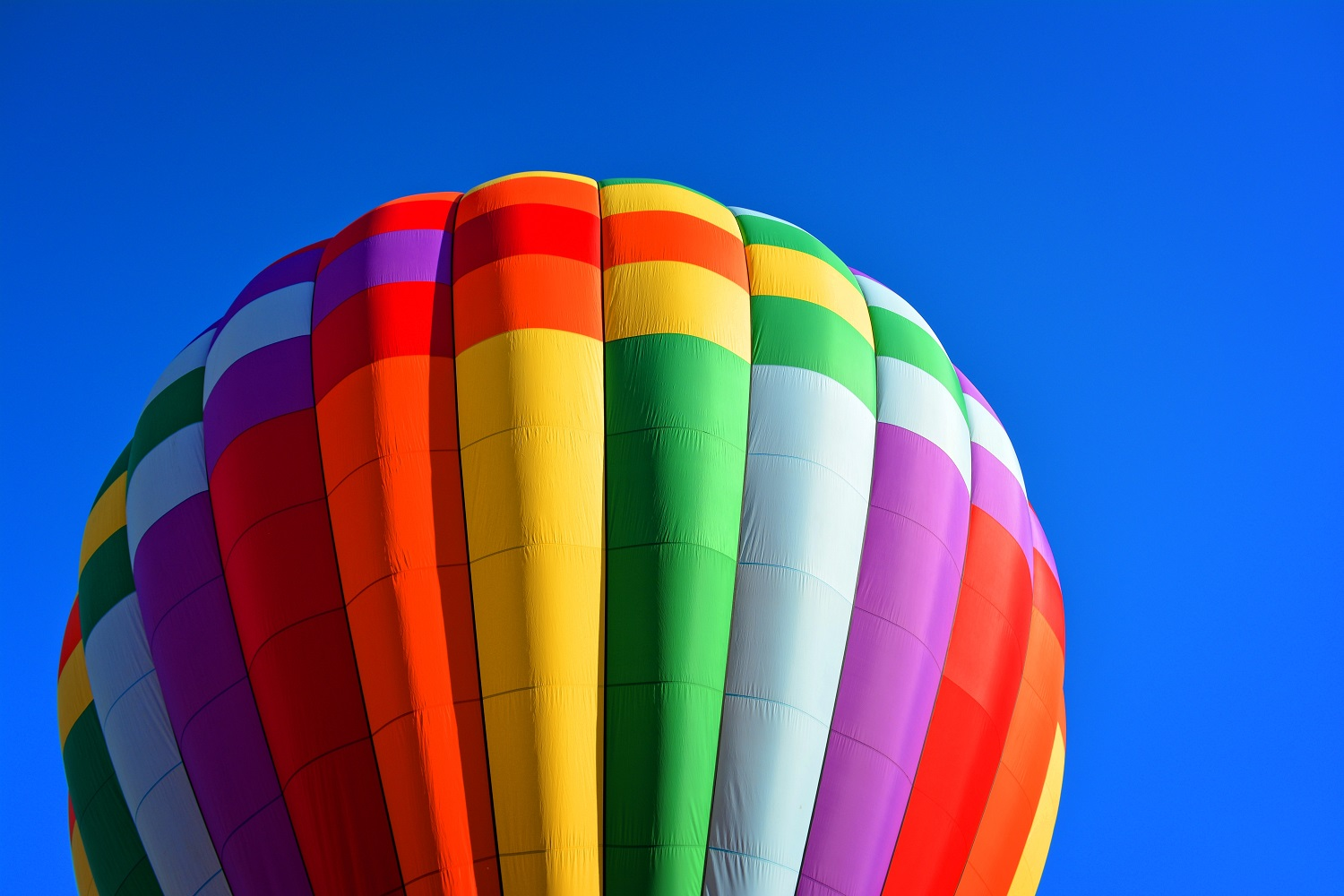Closeup of a rainbow colored hot air balloon floating against a clear blue sky.