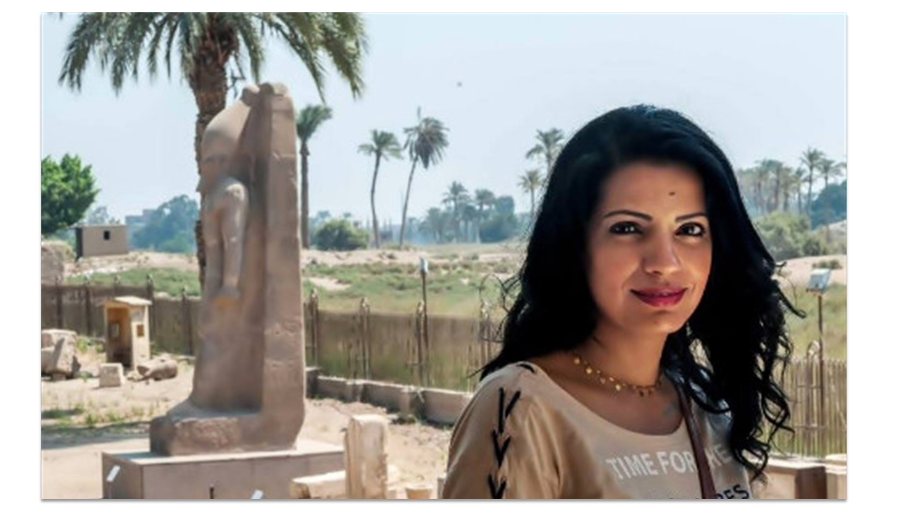 An Egyptian woman stands to the right in front of some Egyptian ruins.
