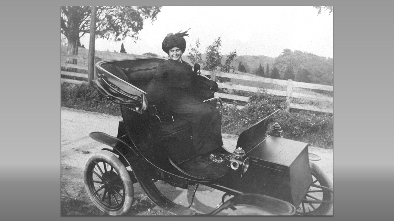 Black and white image of Edith driving her open electric car
