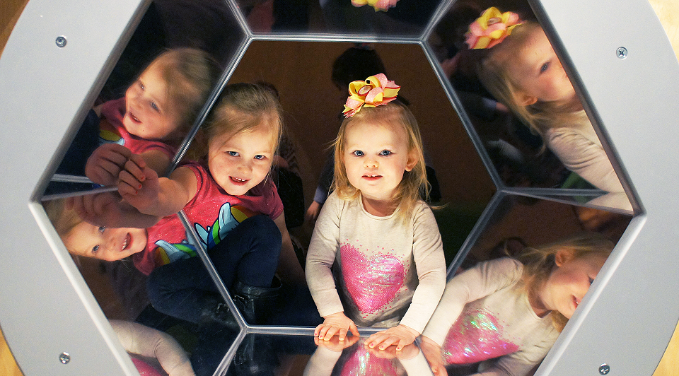 Two children peek through a mirrored hexagonal window.