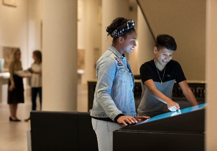 A young black girl and a brown boy look down at an interactive kiosk in the museum.