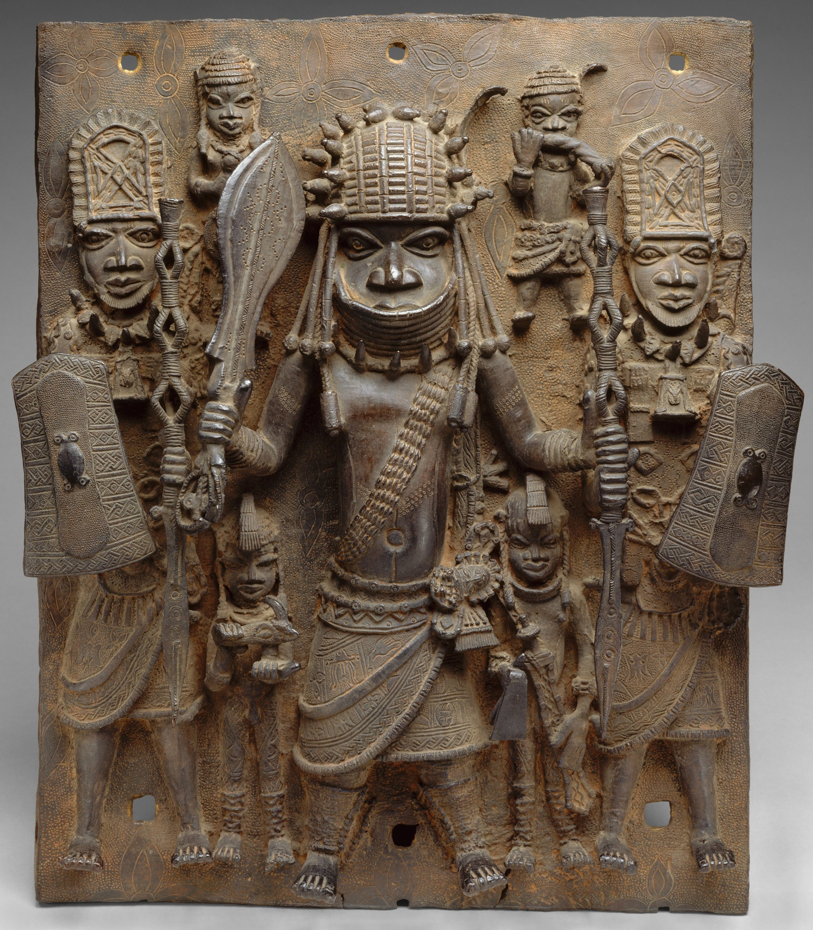 A plaque from Benin featuring what appear to be three soldiers in loincloths headdresses. They are brandishing clubs and shields.