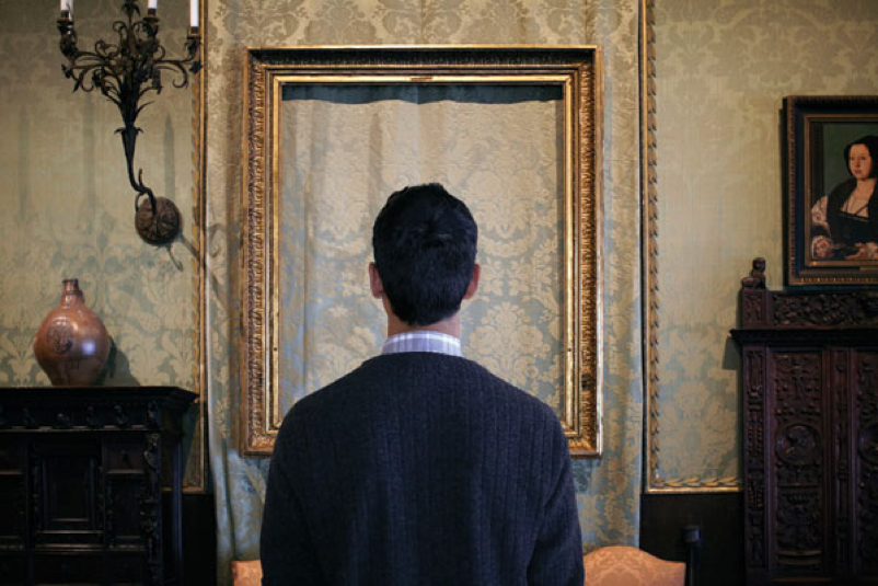 A man faces an empty gold picture frame hanging on elegantly patterned wallpaper.