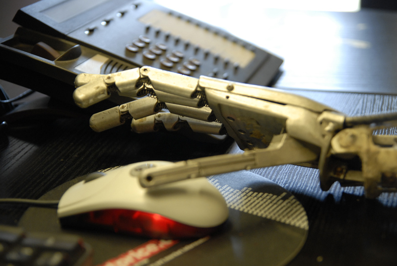 A robotic hand is shown reaching for a computer mouse, with a desktop phone in the background, in a vivid if not entirely accurate illustration of artificial intelligence coming to the museum workplace.