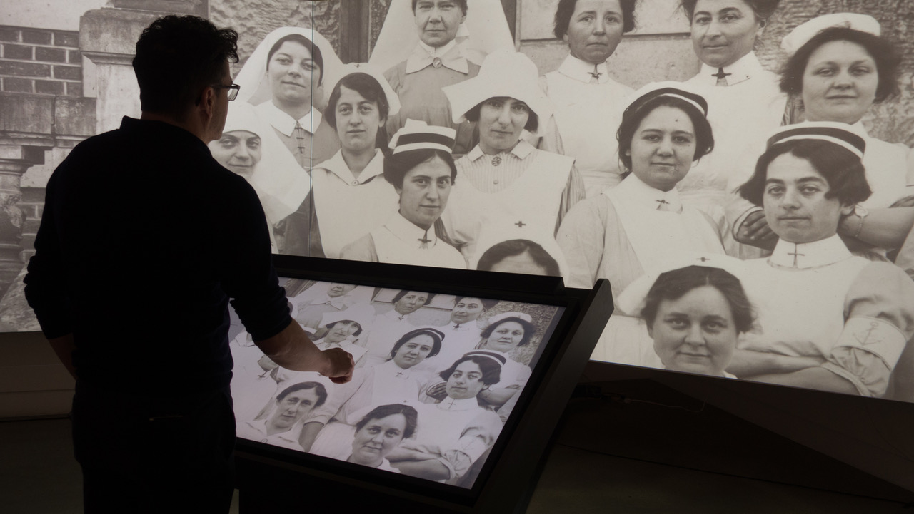 A visitor to the International Center of Photography is seen viewing a historical black-and-white photo of a group of women in uniform. The photo appears on the screen in front of the visitor, which he touches, and in larger size in front of him. Using the touch screen, he is able to change his view of the photograph.