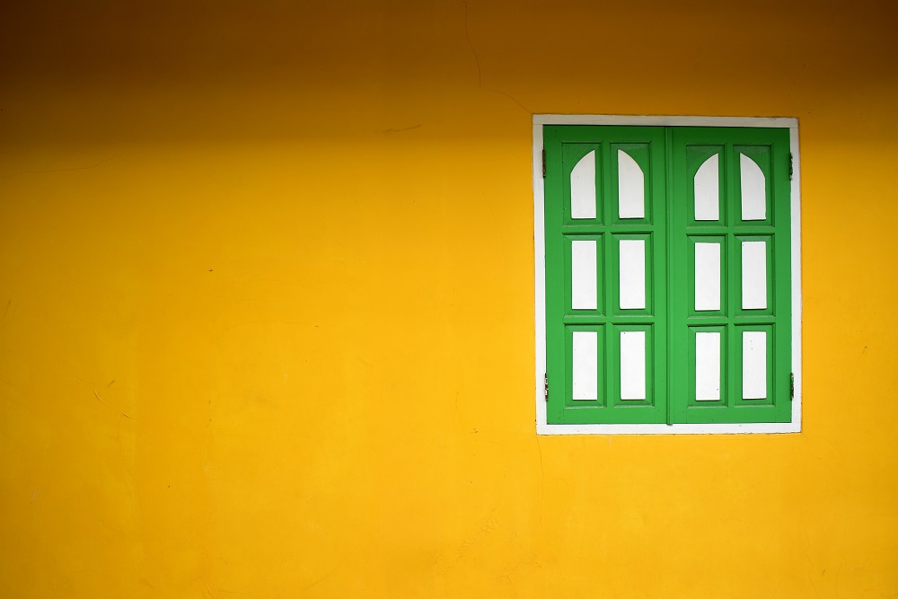 View of a yellow painted wall with a shuttered window painted in green and white off-center on the wall.