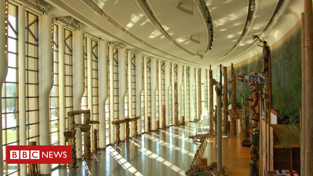 Interior view of the Canadian Museum of History in Ottowa with several totum poles on display throughout a large semi-circular space with a wall of floor to ceiling windows to the left and wooden platforms to the right.