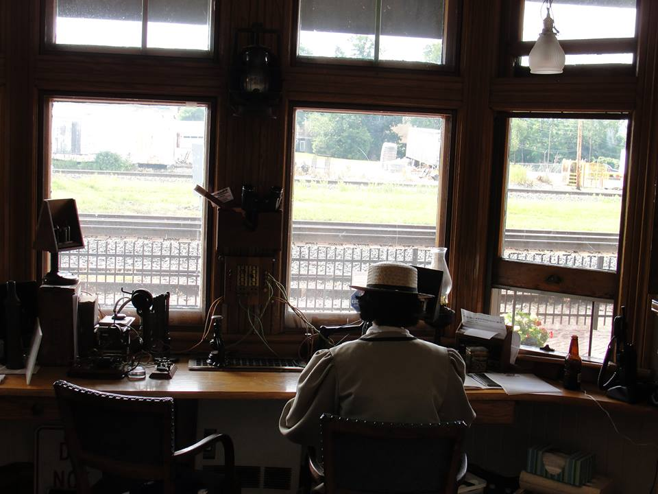 A woman sits at a desk wearing period costume. On the desk is an exhibition of several historical telegraphs. Railroad tracks are visible in the window in front of her.
