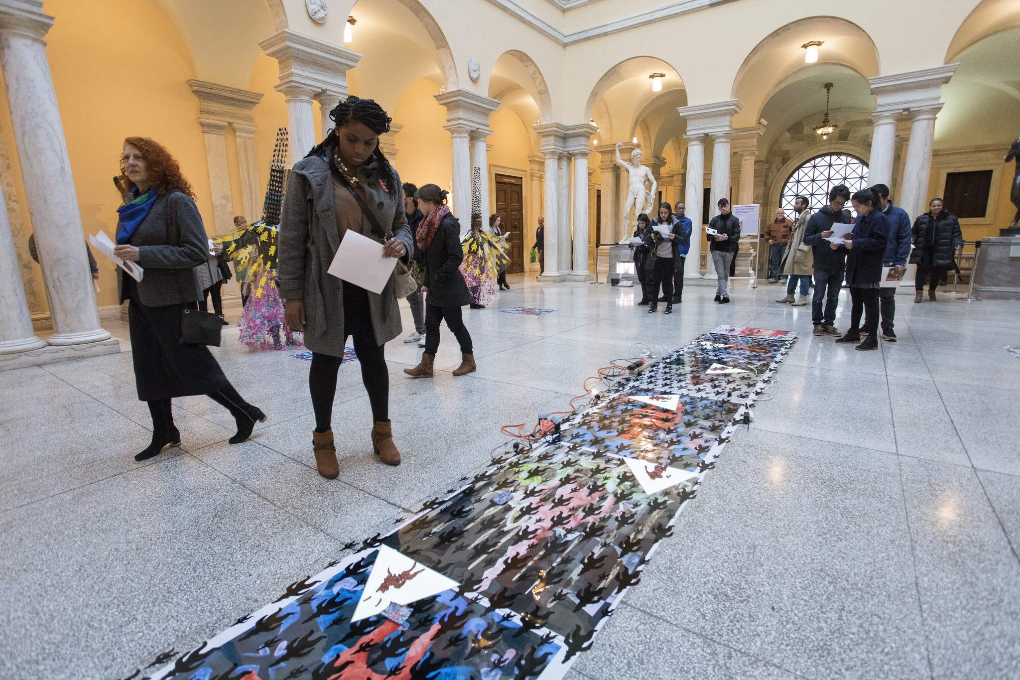 A young black woman stands in a museum inspecting a flat printed piece that is displayed on the floor.