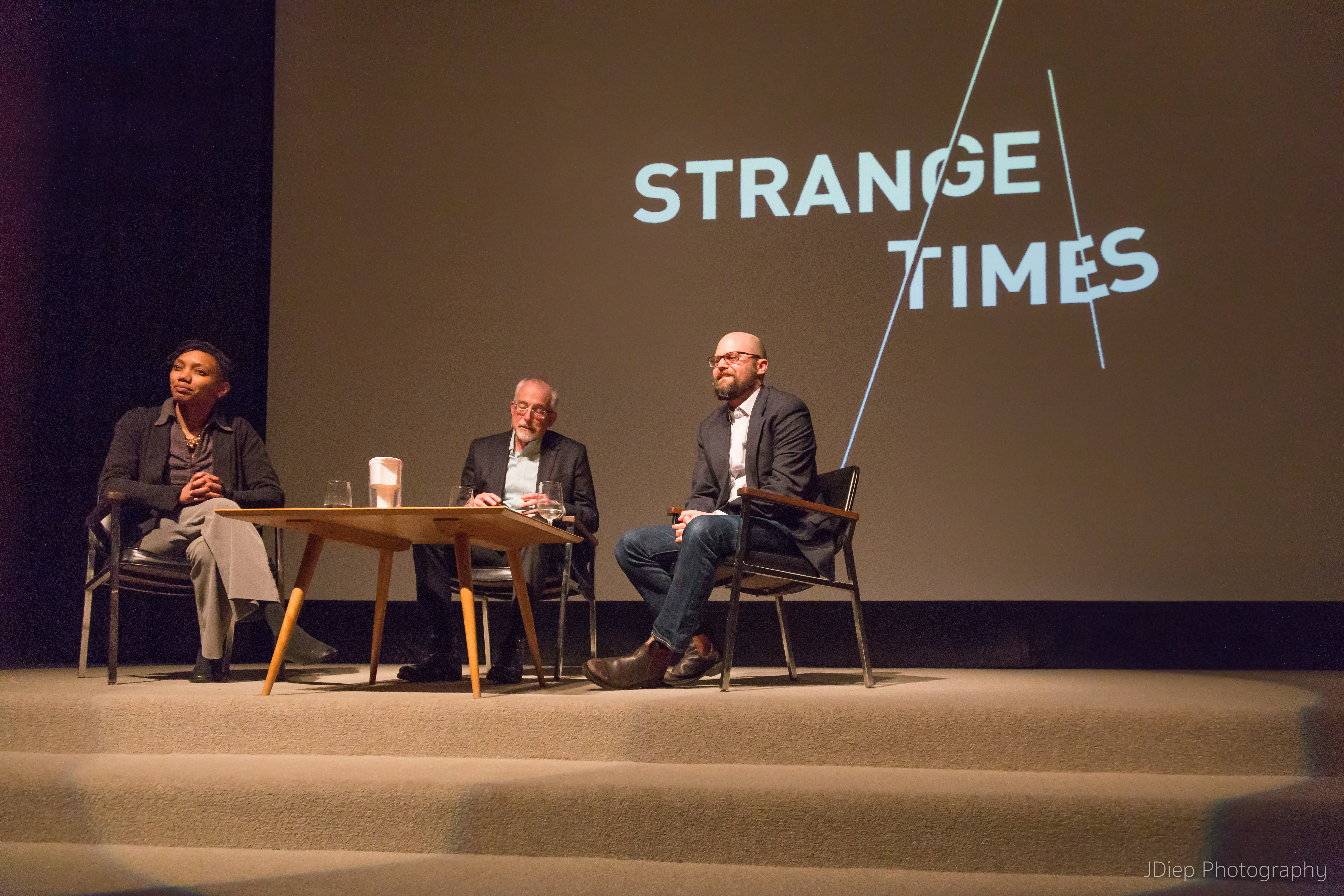 "Speakers sit around a table in front of a screen with the name of the program series, ""Strange Times"""