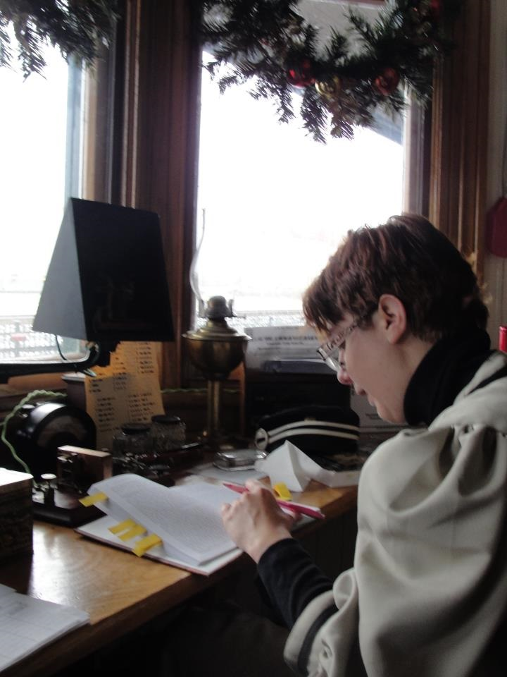 A white woman with short brown hair sits at a desk with a pencil in her let hand looking at book on the desktop which is situated under a set of windows.
