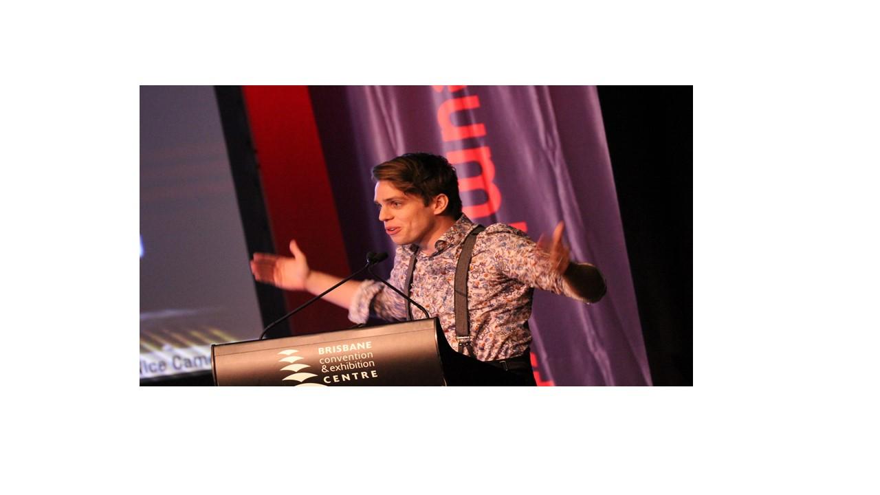 Man wearing suspenders speaking behind a podium