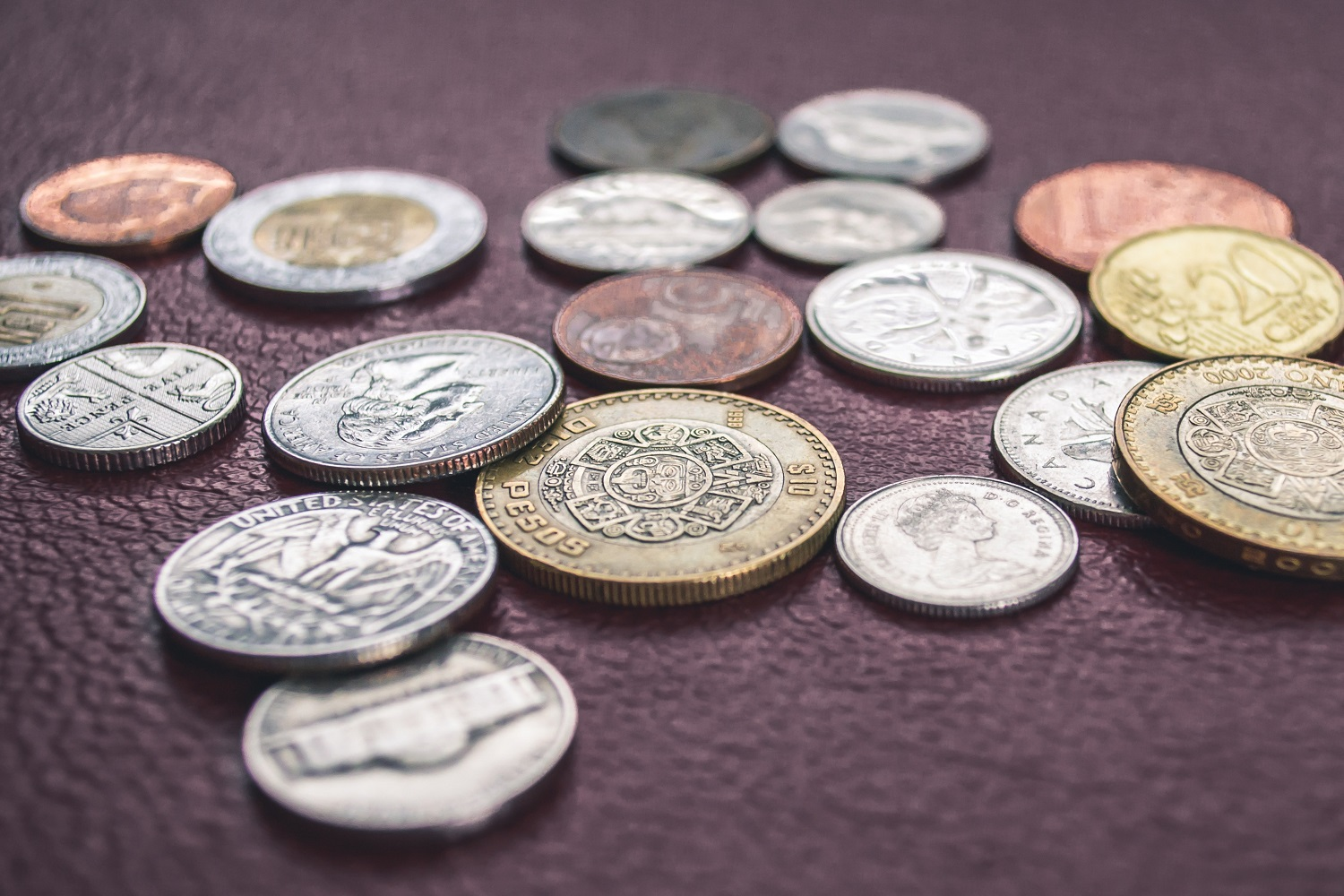 Image of a variety of coin money from around the world displayed next to and one on top of the other on a wooden background.