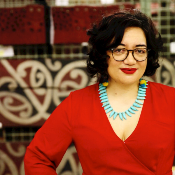 Professional shot of Puawai Cairns a dark haired woman wearing dark rimmed glasses, a red surplice top and turquoises colored necklace standing in front of a decorative tile wall.