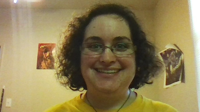 Headshot/selfie of Samantha Silverberg smiling at the camera with short brown hair wearing wire rimmed glasses.