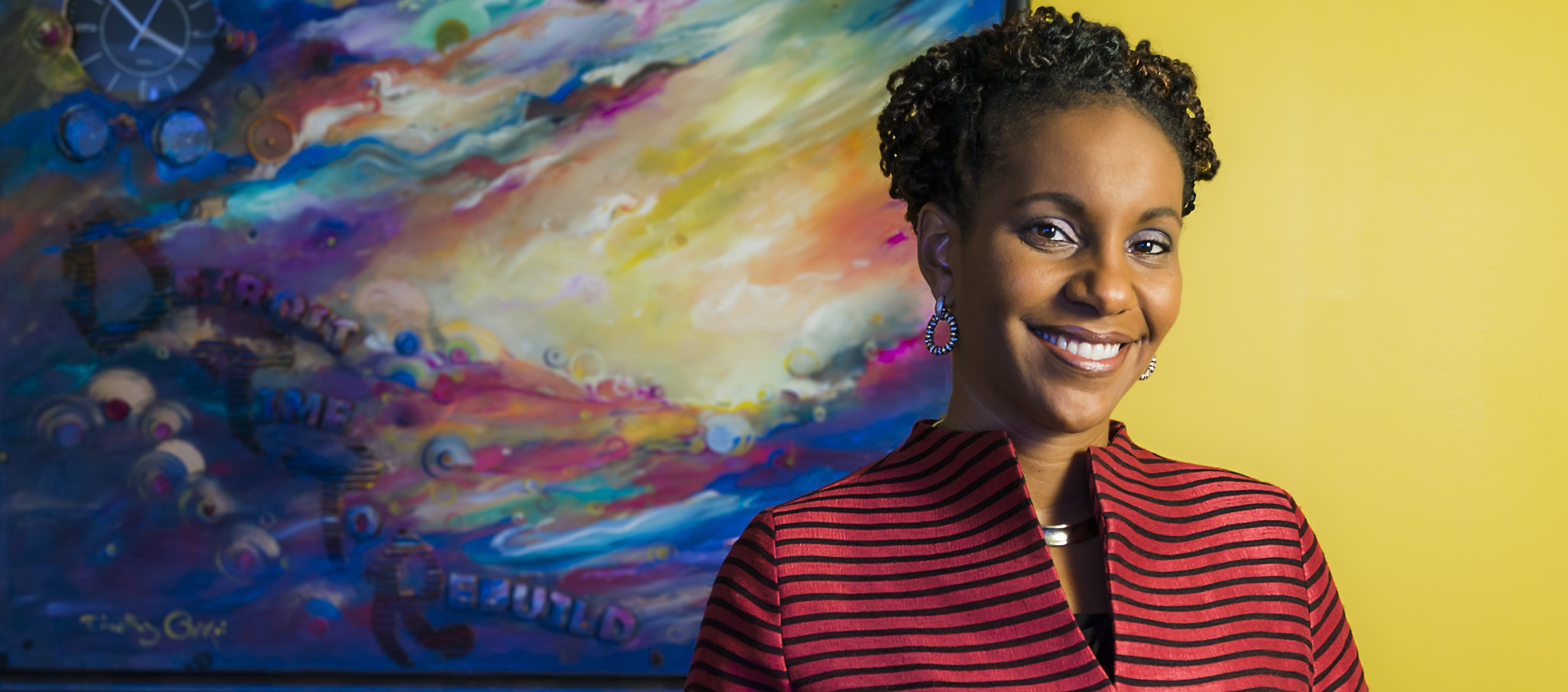 View of Tonya Matthews standing in front of a colorful painting.