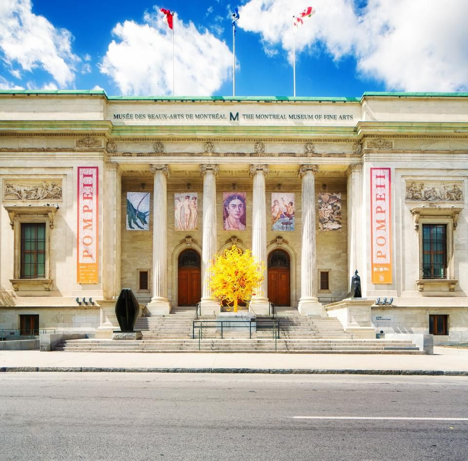 The exterior front facade of the Montreal Museum of Fine Art a classical design with a columned portico and a set of steps.