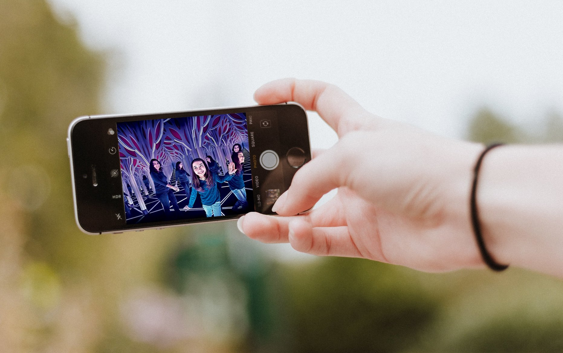 A person's hand holds a smartphone displaying a photograph of one child and one adult frolicking in a mirrored art installation that appears to stretch into infinity, an example of the sort of installations that attract outsize attendance and social media pickup.
