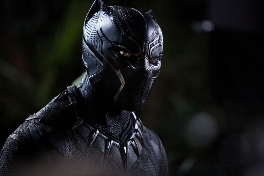 A still photograph of the Black Panther character T'Challa in superhero costume, which is black, sleek, and spiky.