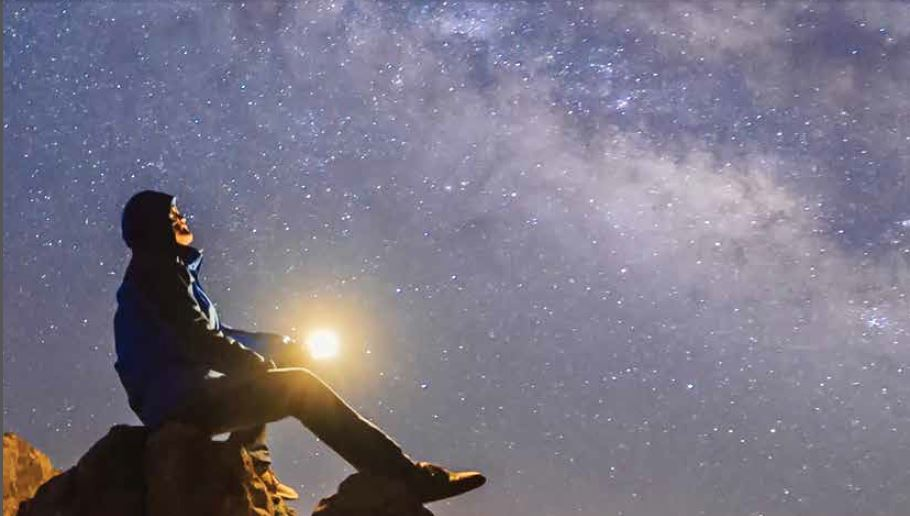 A man sits on a large rock at dusk staring up at the stars shining brightly above.