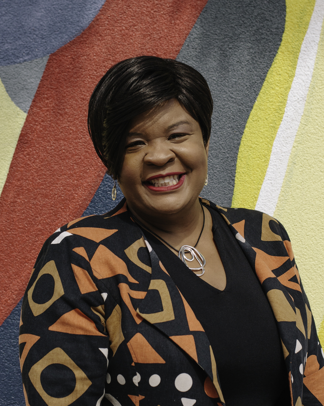 Image of a black woman with straight short black hair standing in front of a colorful backdrop, smiling and wearing a geometric patterned jacket.