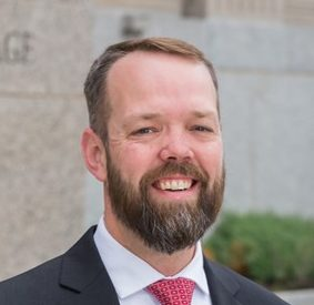 Headshot of a white man with a full beard and mustache smiling at the camera standing outside near a large wall wearing a suit and red tie.