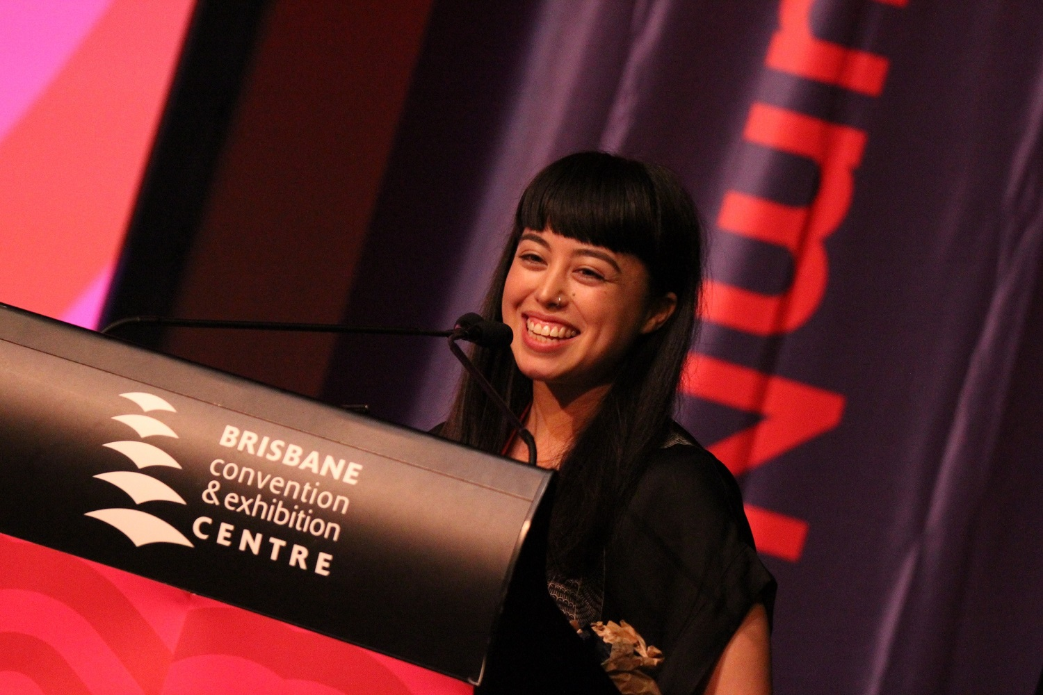 Slightly off-center (tilted to the right) image of a woman with dark hair smiling widely standing behind a podium that says Brisbane convention & exhibition centre.