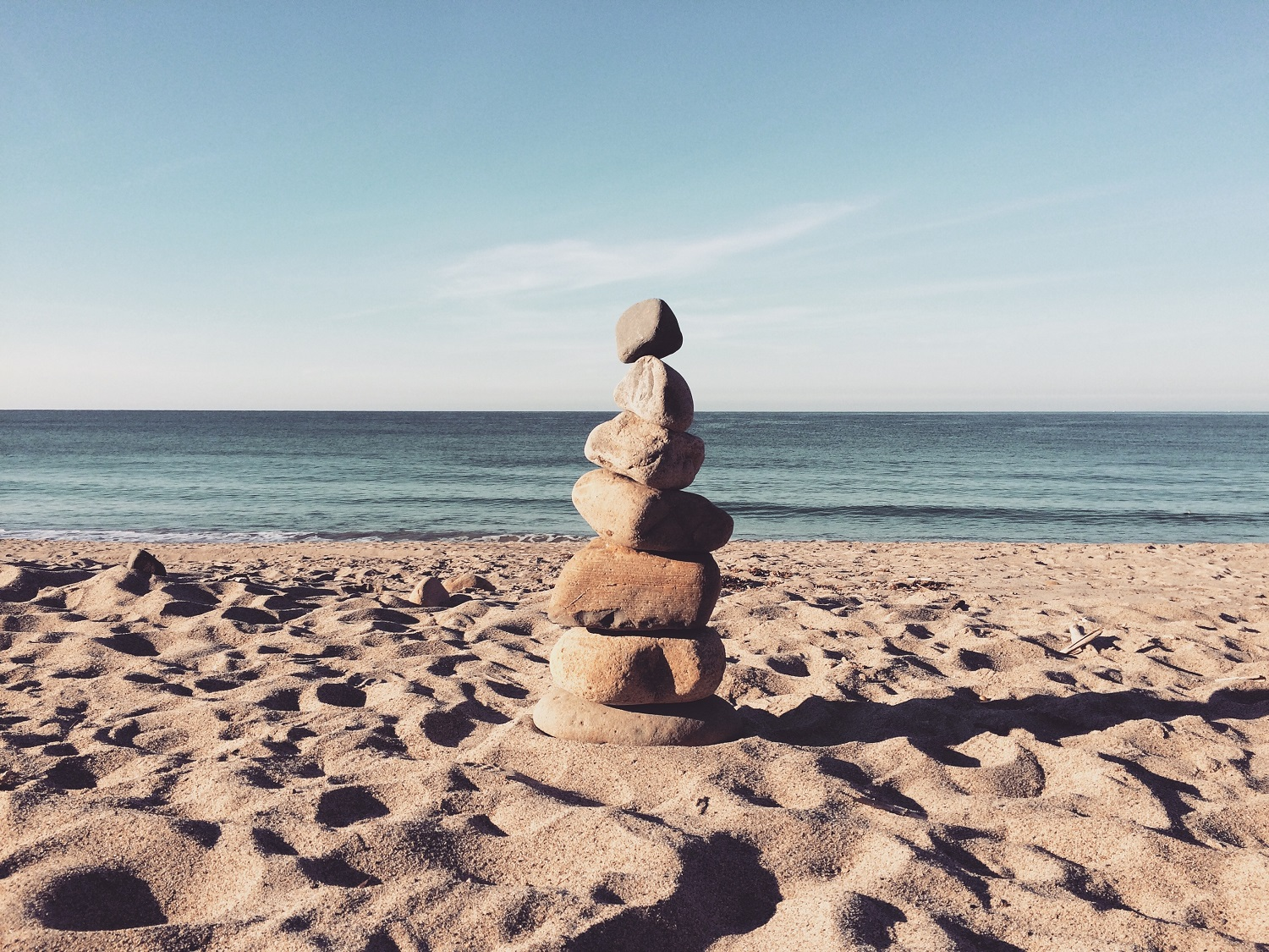 A rock tower standing on a beach in front of the ocean.