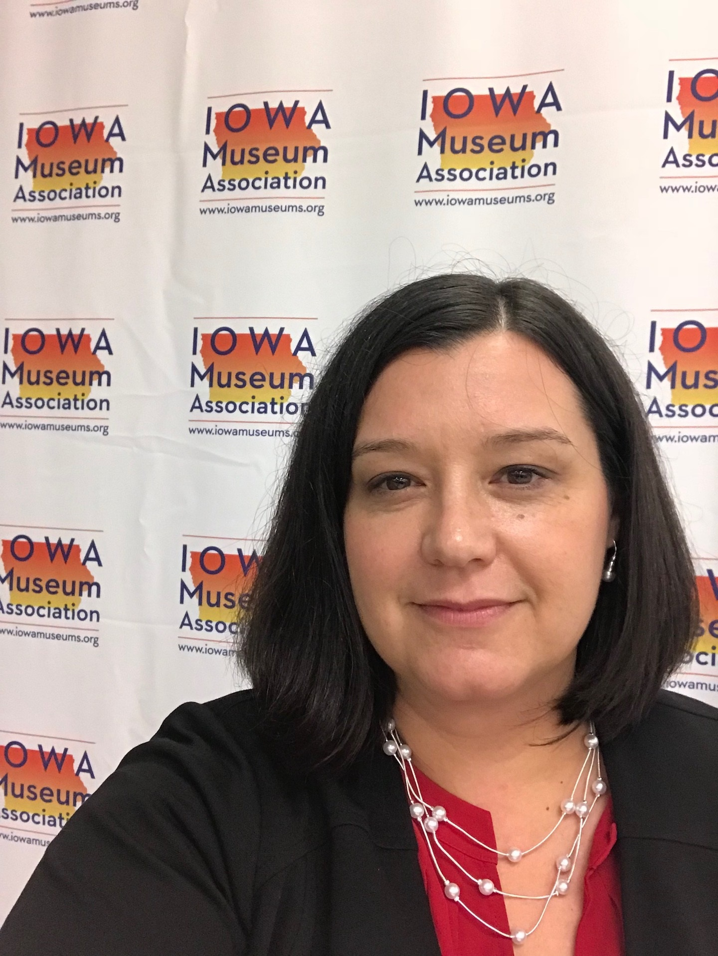 Image of a white woman standing in front of an Iowa Museums Association step and repeat. She has shoulder length brown hair combed to the left side wearing a dark colored jacket and red shirt.