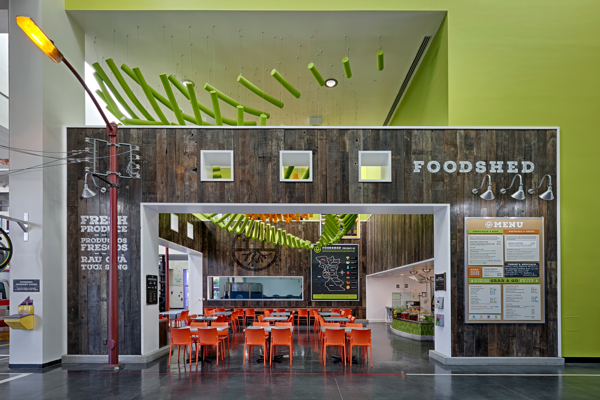 "The FoodShed café has wood walls and brightly colored seating and sculptures, and advertises ""fresh produce."""