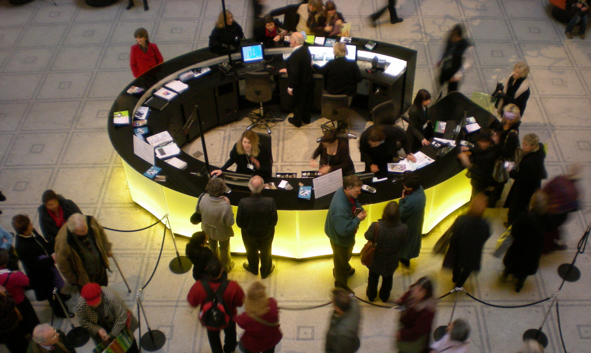 A crowded circular information desk in a museum lobby.