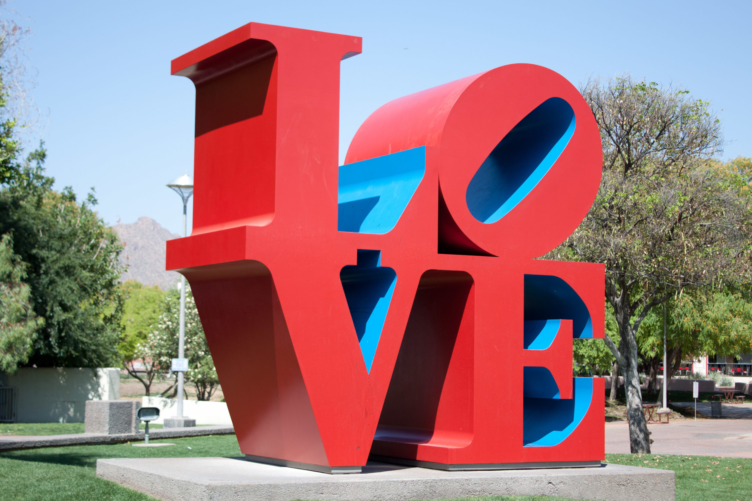 "A sculpture of the famous ""LOVE"" logo by Robert Indiana, where the L and O are stacked on top of the V and E, and the O is slanted sideways. The sculpture is displayed outside with trees and a street visible in the background."