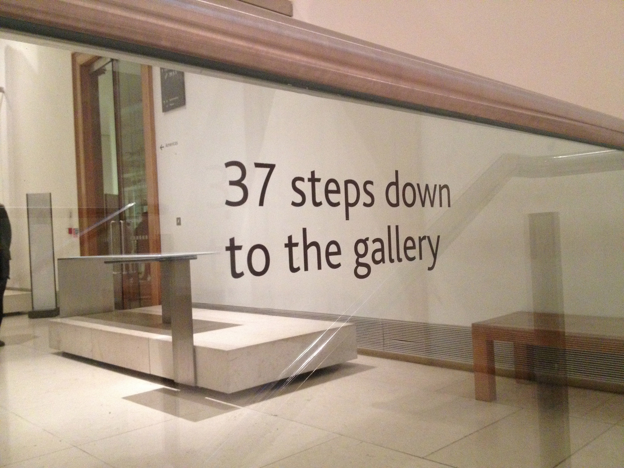 "At the top of a staircase in a museum, a sign advises that there are ""37 steps down to the gallery."""