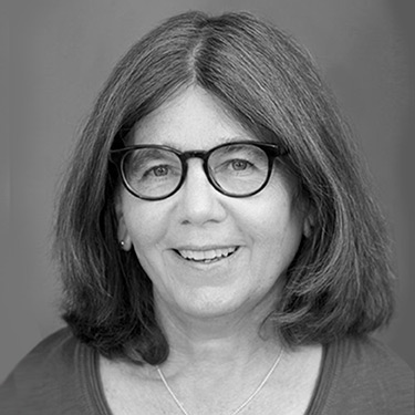 Black and white headshot of Joan Baldwin a white woman with shoulder length brown hair wearing dark rimmed glasses
