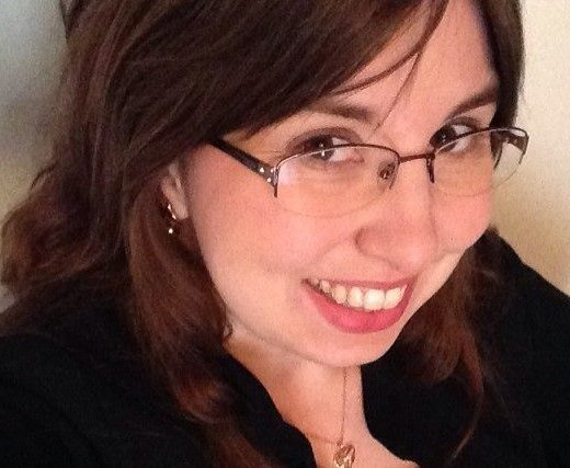 Headshot of Tiffany Rhoades Isselhardt, a white woman with long dark brown hair wearing light rimmed glasses.