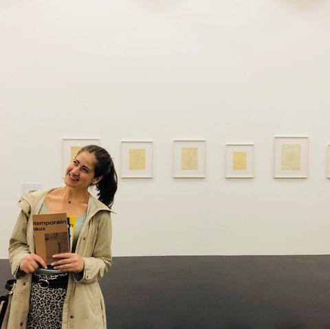 Image of Angela Gala standing in a gallery in front of a series of framed artwork.