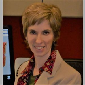 Headshot of Anne Basham standing in front of a computer which is off to the left hand side of the screen. She is a white woman with short cropped hair wearing a tan suit jacket and colorful patterned top.