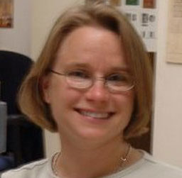 Headshot of Donia Conn, a white woman with short blond hair wearing wire rimmed glasses.