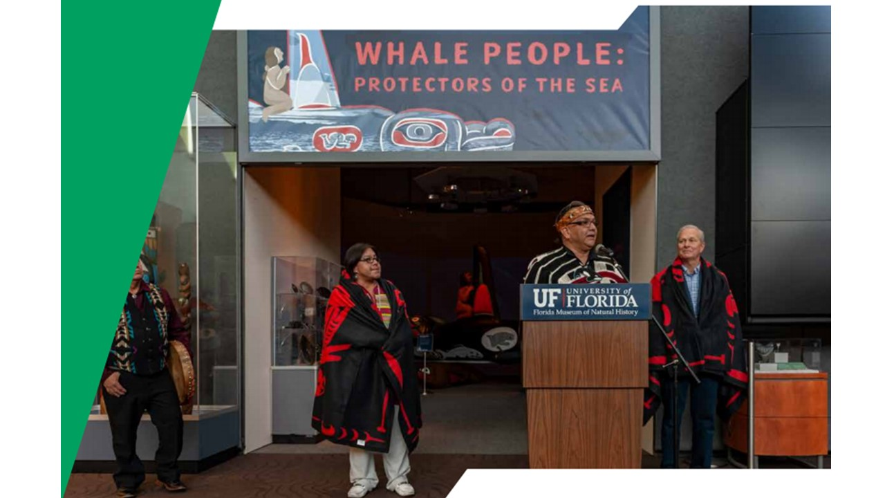 Several indigenous people stand ourtside of the Whale People Protection of the Sea exhibition.