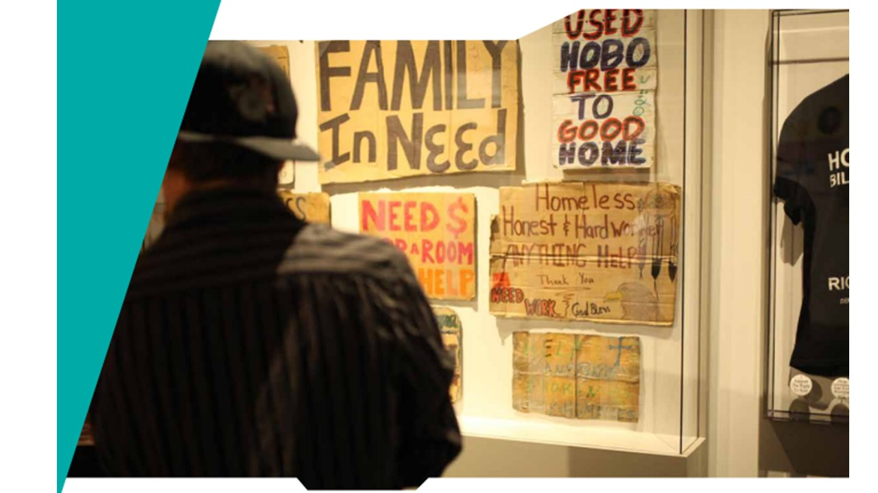 A man stands facing a wall with various handwritten signs from people who have experienced homelessness.