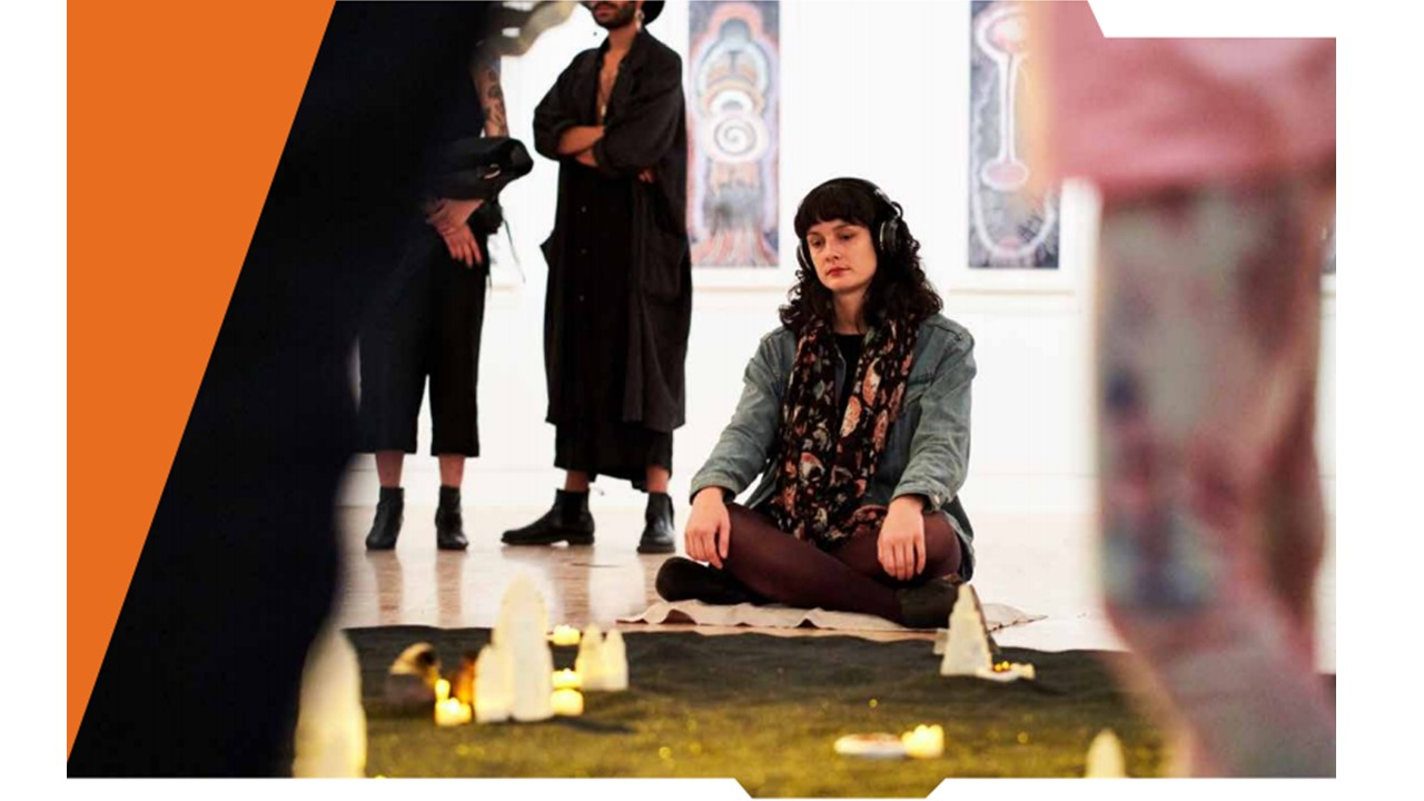A woman sits crosselegged on a towel on the floor wearing headphones in front of a set of candles as other people mill around to the right hand side of the image chatting.