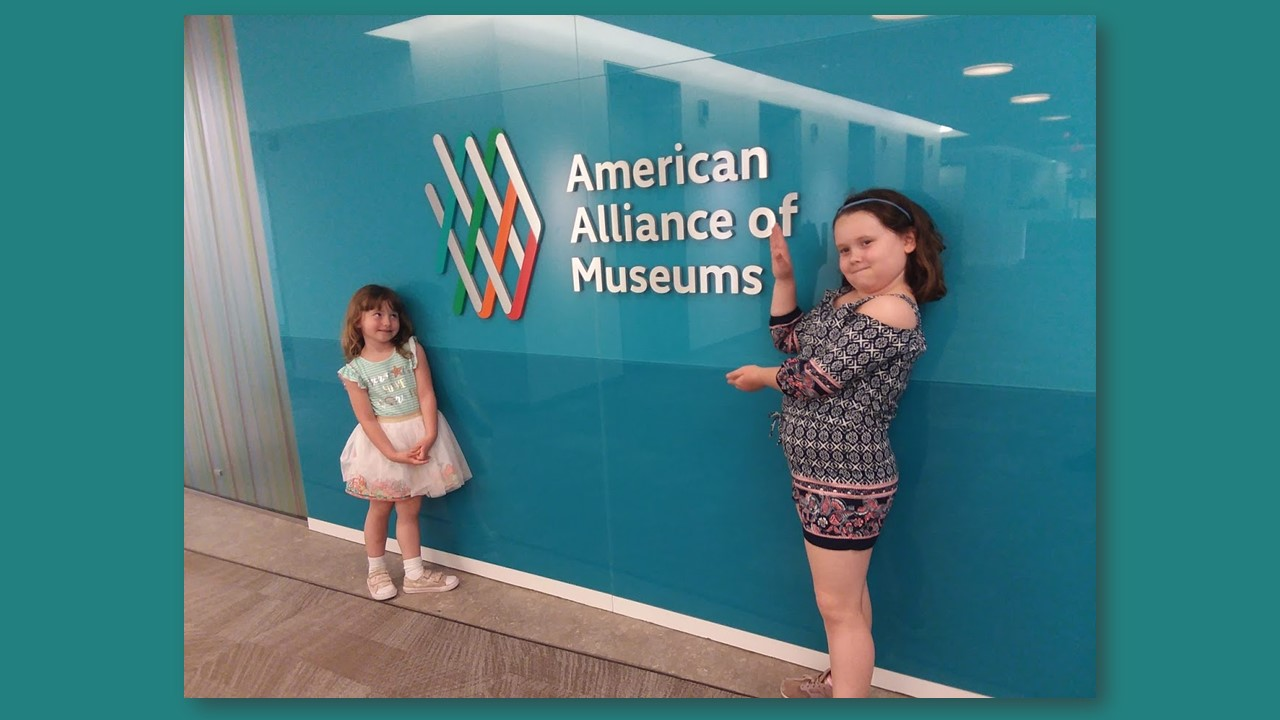 Two young white girls stand in front of the American Alliance of Museums logo and sign
