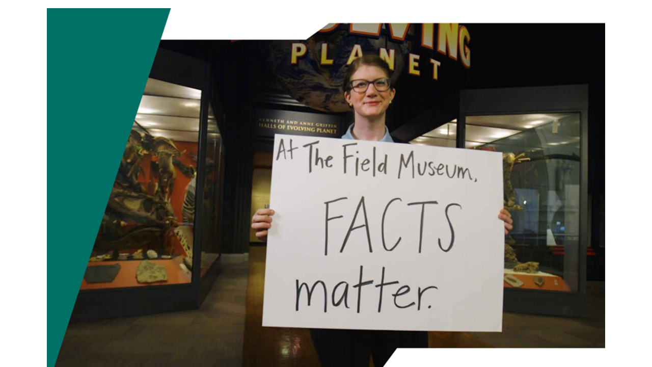 "Emily Graslie, Field Museum Chief Curiosity Correspondent stands in front of an exhibtion on the planet earth with a handwritten sign that says 'At The Field Museum FACTS matter""."