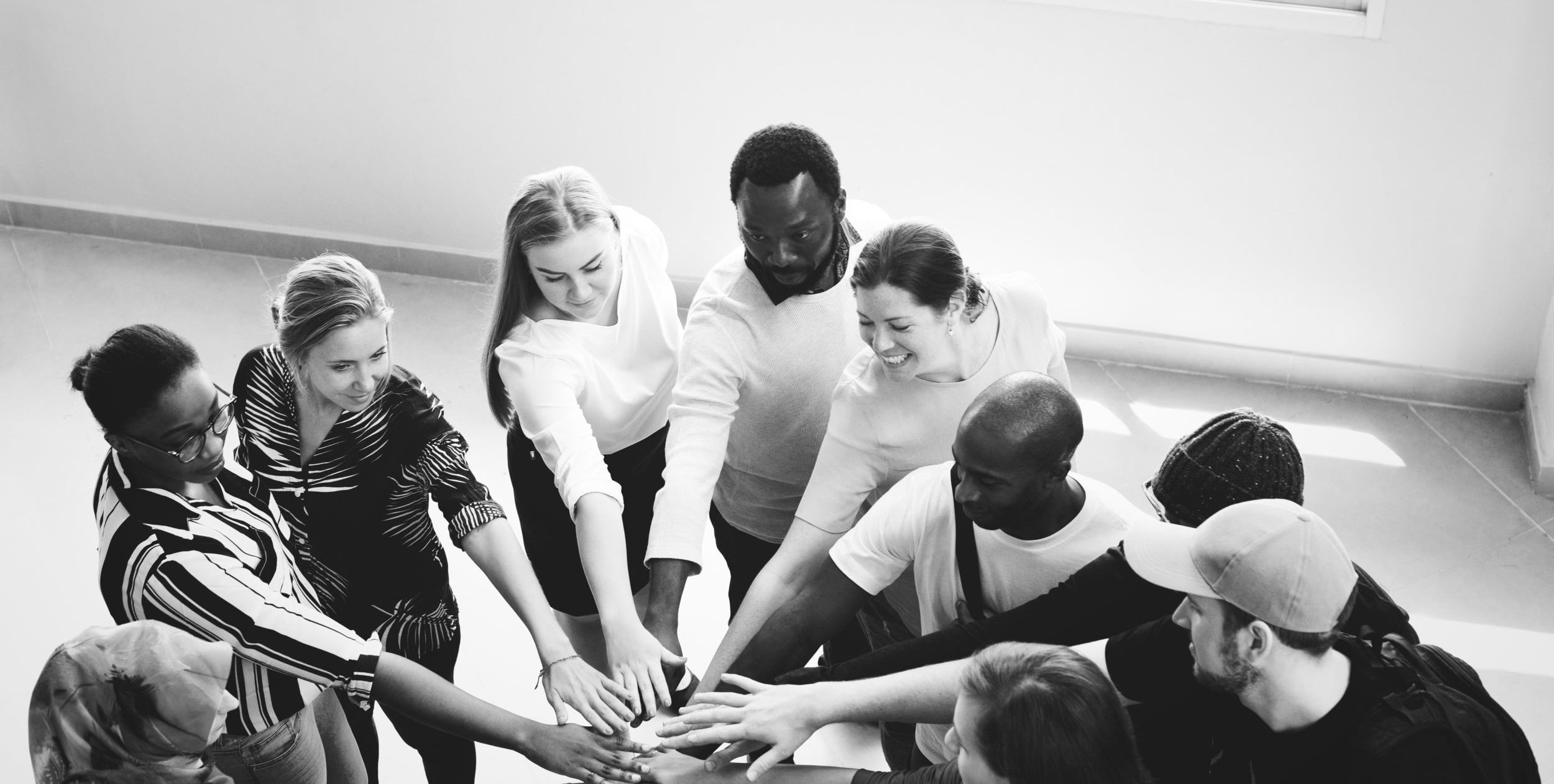 A black-and-white photo of a group joining hands in a circle, an expression of teamwork.