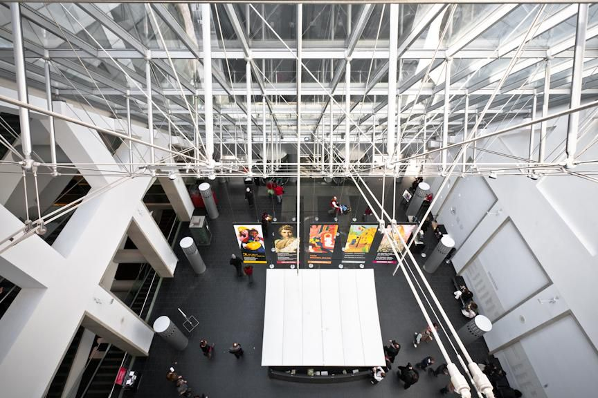 An aeriel shot of the Desmarais Pavilion at the Montreal Museum of Fine Arts. There are industrial architectural features below the ceiling that appear to be metal scaffolding, white walls, and a black floor with brightly colored artworks along the walls of the room.