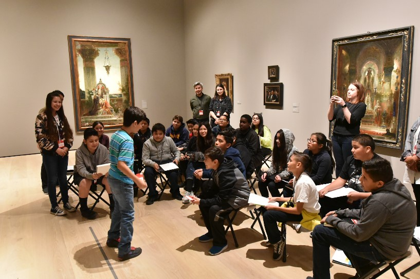 A young visitor stands in front of a larger group of visitors in a gallery.