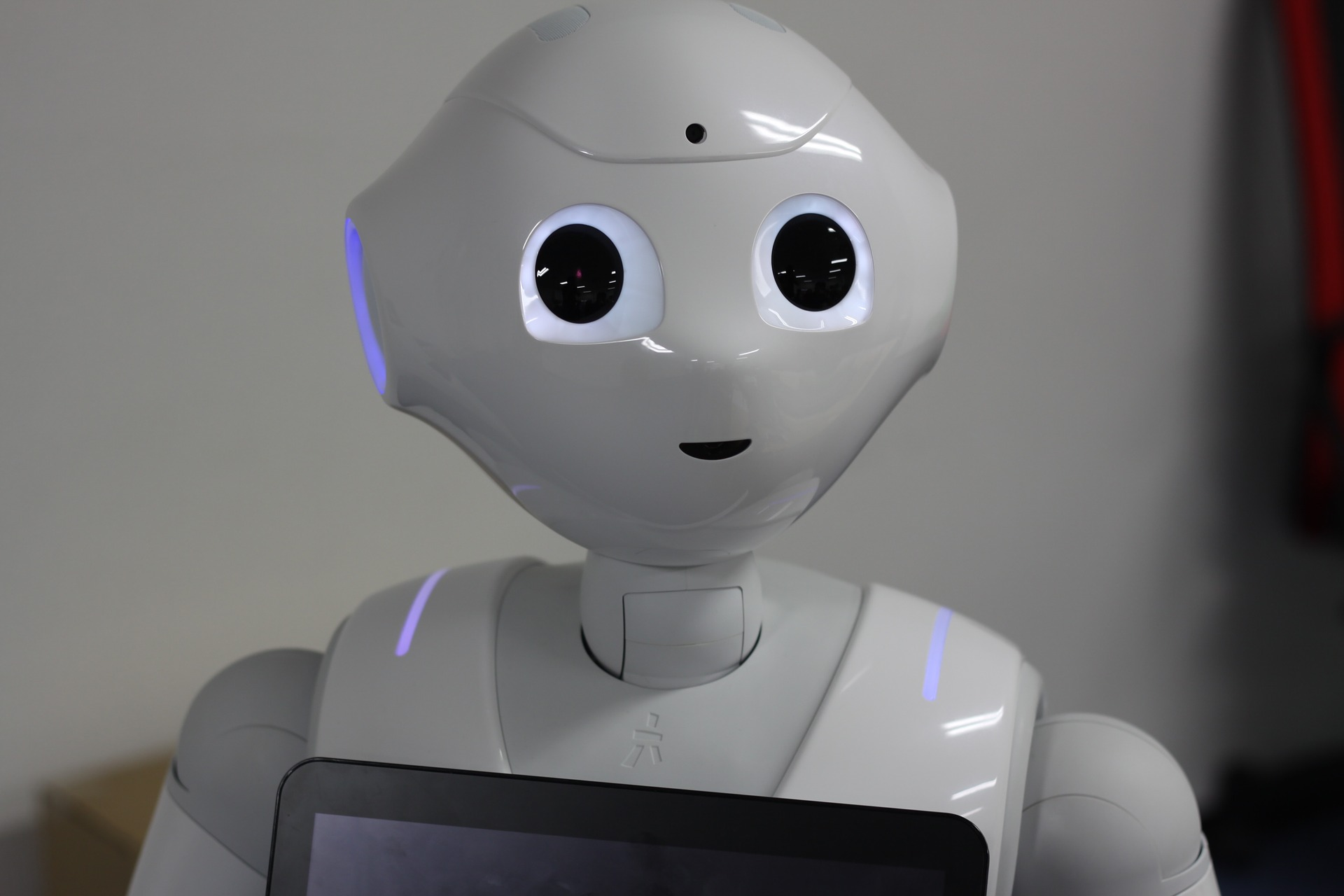 A plastic white robot with humanoid features and a touchscreen attached to its chest.